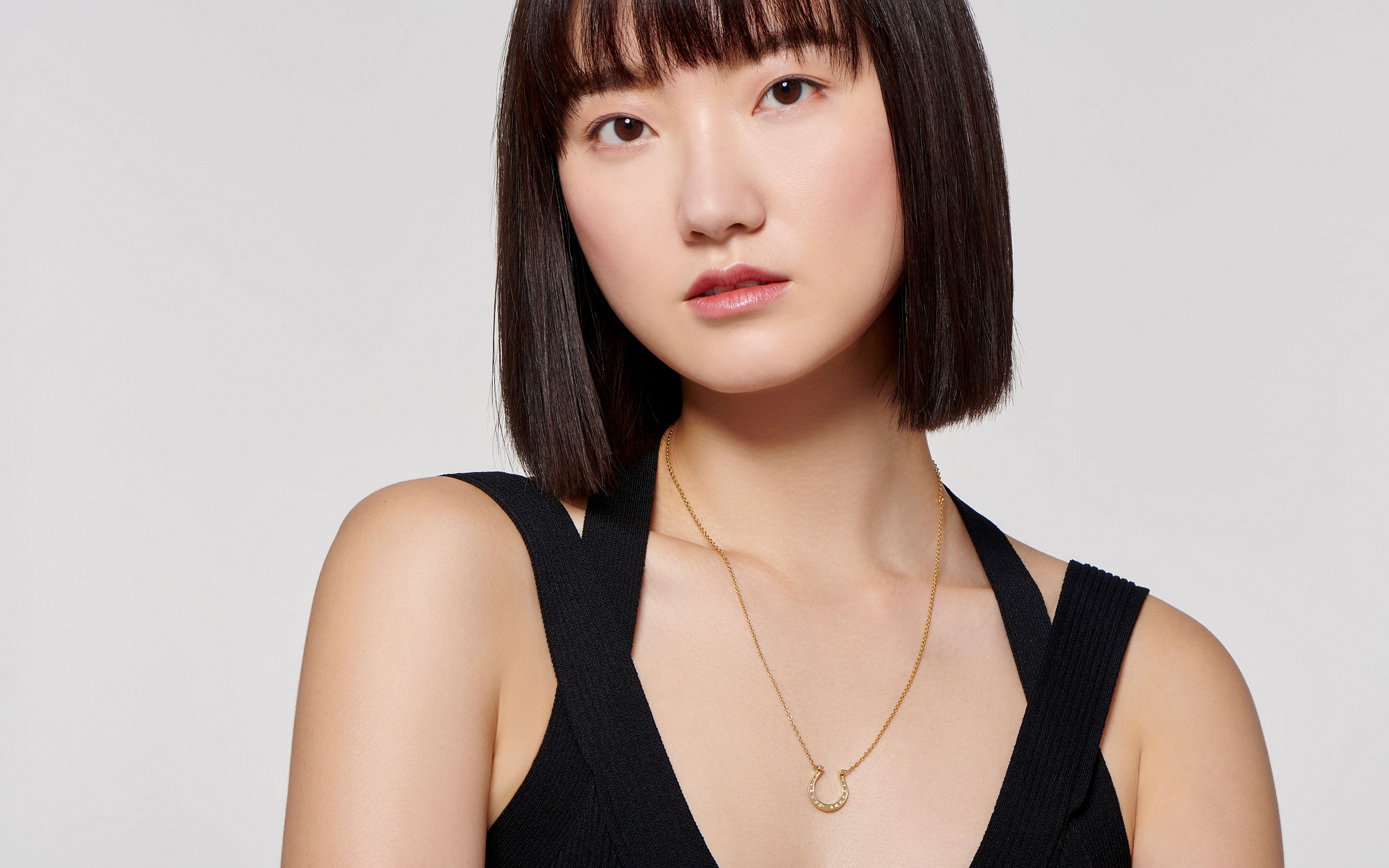 Refined Asian woman wearing a sleek horseshoe pendant 22 karat gold necklace delicately studded in 14 round diamonds