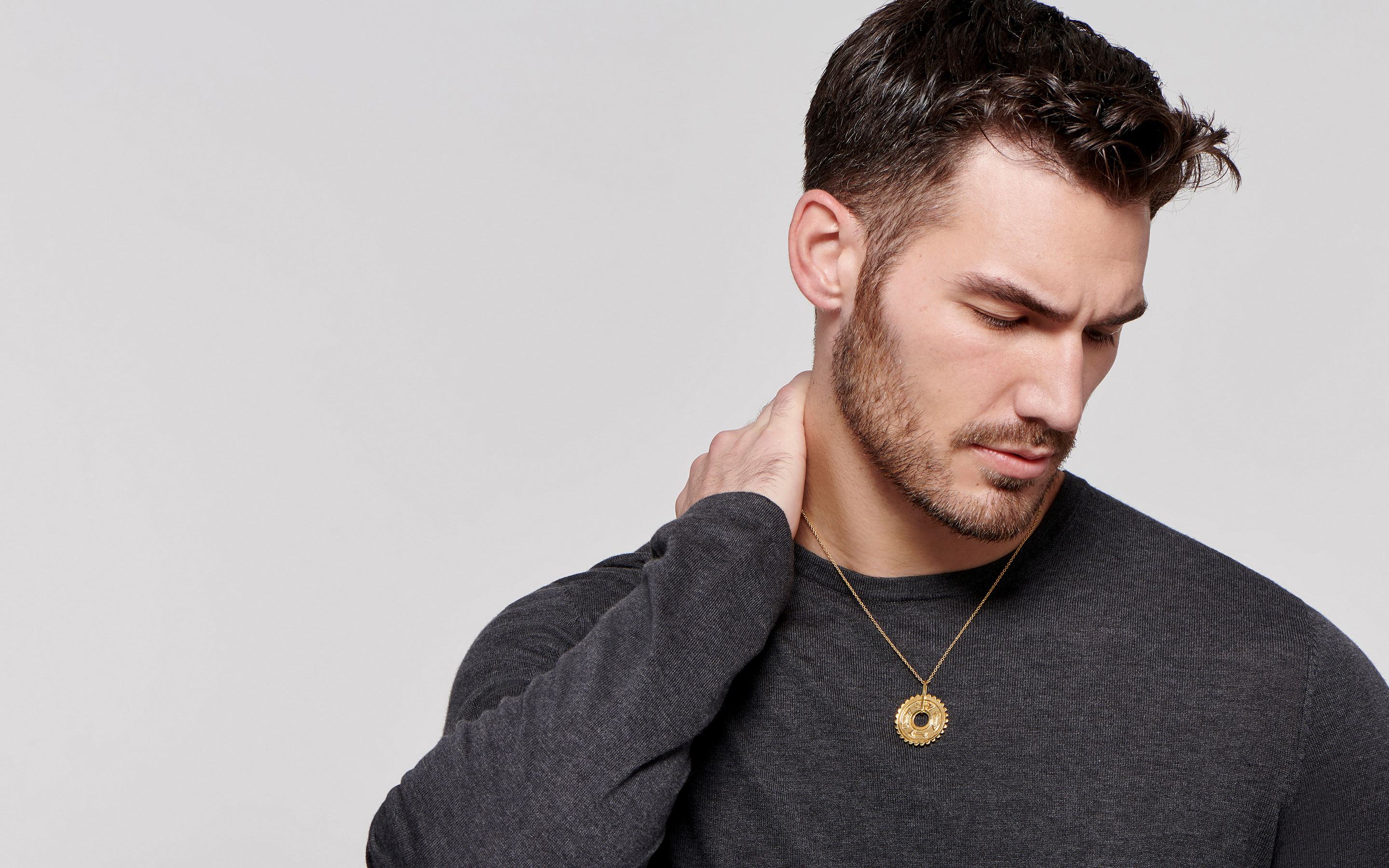strong male model wearing an artisan crafted 22 karat gold medallion