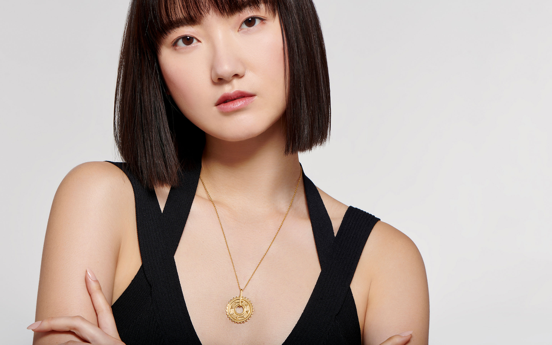 beautiful female Asian models a luxurious 22 karat gold medallion