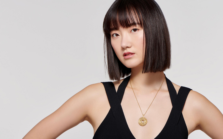 Fabulous Asian woman displays a breathtaking 22 karat gold talisman necklace