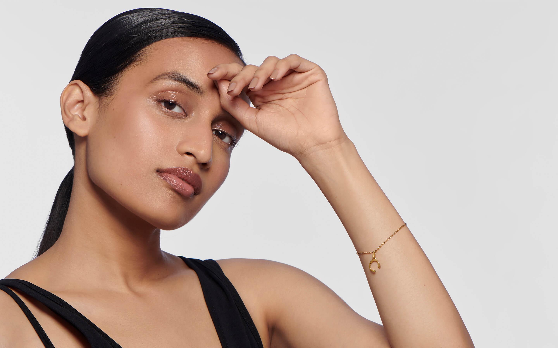 Woman model wearing 22 karat gold alphabet pendant