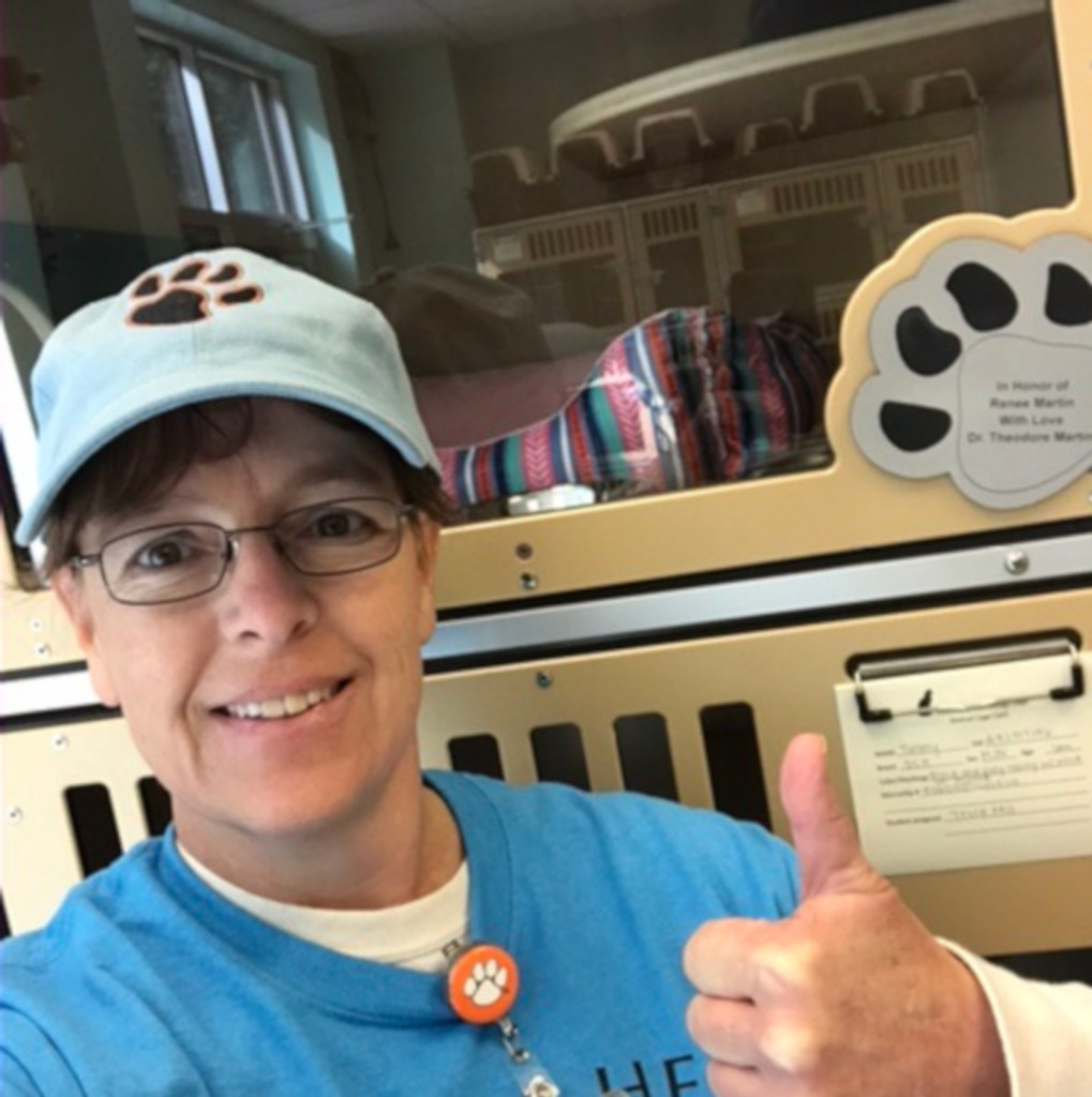 Tri-County Technical College Vet Tech program's director next to their Gator Kennels Cat Hotel.
