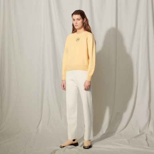 yellow sweater with logo by sandro paris