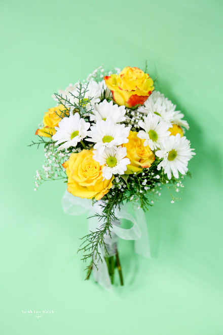 Happy spring bouquet of yellow roses, white daisy, baby's breathe and touch of carolina sapphire, just what is needed after a long winter.
