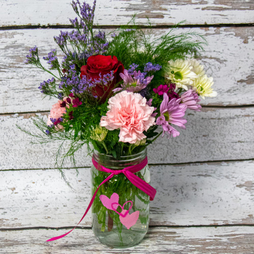Mixed pink, purple, and red, fresh flowers in Valentine Colors arranged in a colored clear mason jar with pink hearts.
