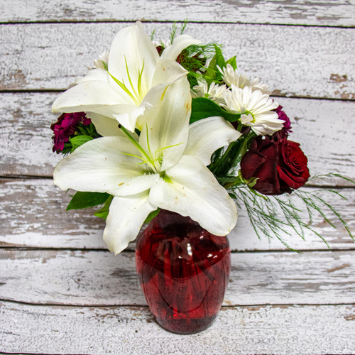 One of our most popular romantic arrangements! A red vase filled with white stargazer lilies, red roses and white daisies designed with a romantic look and feel, and will smell even better!