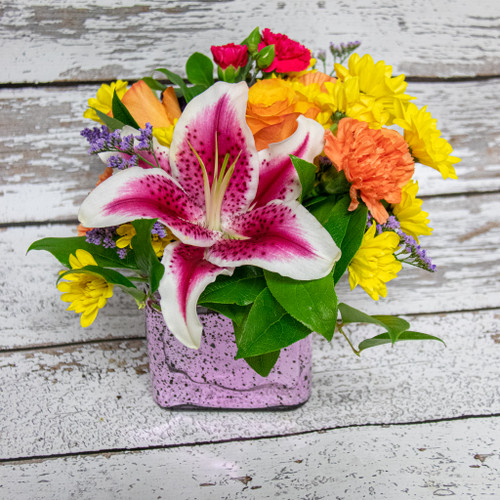 A unique arrangement in a pink cube with a little bit of added sparkle featuring bold and fragrant Stargazer lilies, orange roses and other orange and yellow accent flowers.