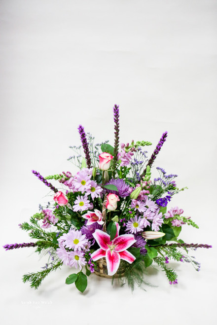 A wicker basket of purple and pink flowers accented by an amazing stargazer lily adding tradition and fragrance to a thoughtful remembrance.
