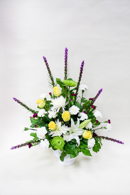 A unique combination of calming whites and purples, accented with a pop of yellow roses and lime green spider mums in a traditional one sided spray.