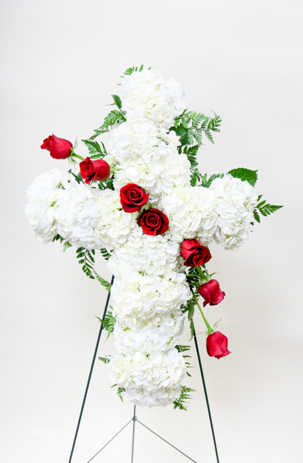 A dramatic white floral cross of white hydrangeas with accent of red roses.