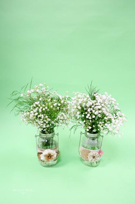 Simple baby's breath mason jar wedding centerpiece with  brides burlap decor.