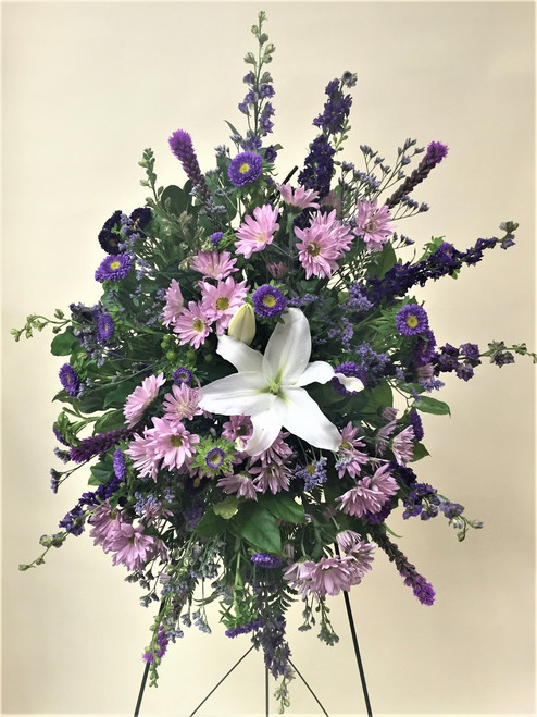 Beautiful mix of lavender and purple fresh flowers designed in a standing easel. Accented with locally grown white lilies!