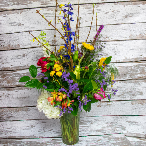 A Gorgeous unique fresh flower arrangement. Perfect for making a statement with local grown sunflowers and Lilies, mixed with premium roses and blooming branches.