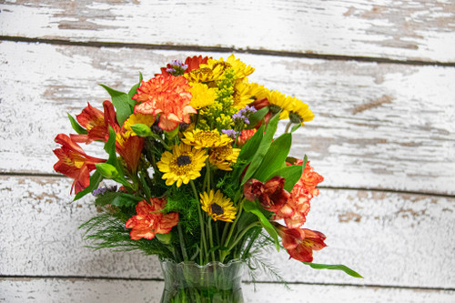 A simple mixed fall arrangement in a clear vase, including mums, carnations and alstroemeria.