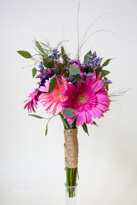 Mix of wild grasses and eucalyptus coordinates with hot pink gerberas.