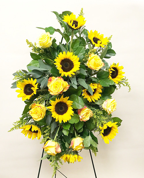 A easel spray designed with locally grown fresh sunflowers and high end yellow roses.