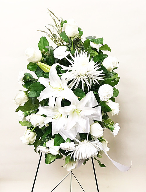 A traditional white easel spray arrangement made with a mixture of white fresh flowers and locally grown liles.