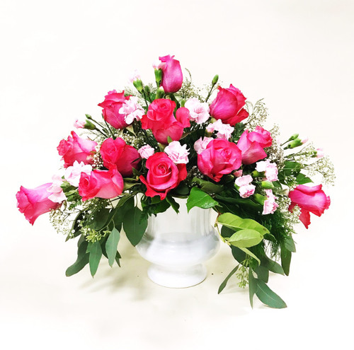 A bold and bright garden style tribute of roses and mini carnations.