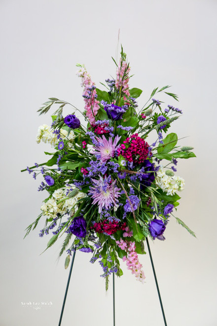 A sophisticated standing easel spray of purples and pink feminine colors.