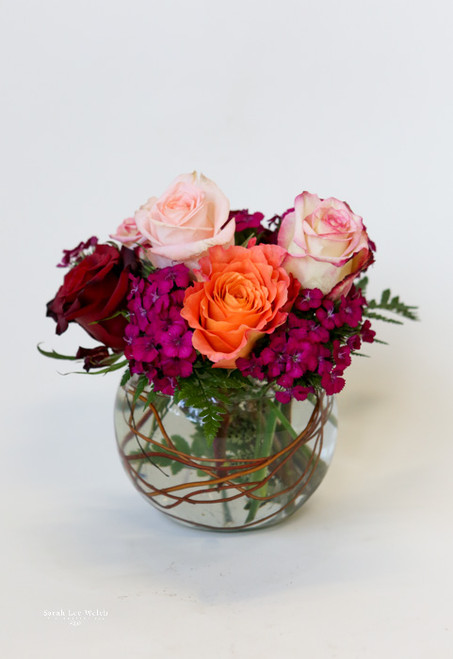 A charming arrangement of different colored roses in a small, round, bowl accented with willow branches in the water.