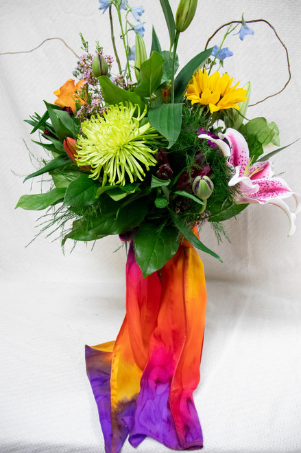 Send her a stunning mix of Spring Flowers designed in a premium vase of mixed seasonal flowers and add a bright silk scarf! Give her the gift of style with these local artist hand painted scarves from Silk Sensations.