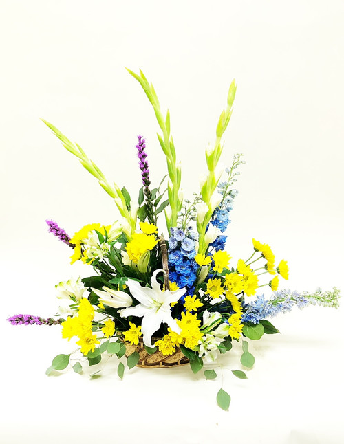 Send something bright to the service with this beautiful yellow, purple and blue spray.  Designed one-sided in a basket in a fan shape, this arrangement includes flowers like delphinium, mums, lilies and other accent flowers.