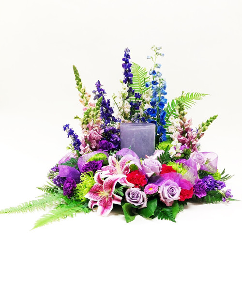 Gorgeous pink and purple mixed flowers styled as a round wreath styled sympathy spray. Designed with locally grown lilies and  premium purple roses.