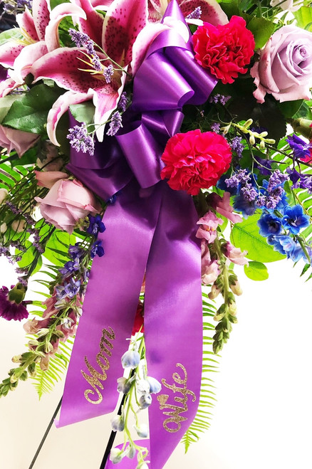 Gorgeous pink and purple mixed flowers styled as a standing easel sympathy spray. With locally grown lilies, premium purple roses, hot pink and purple carnations and other accent flowers, this is a perfect tribute to someone special.