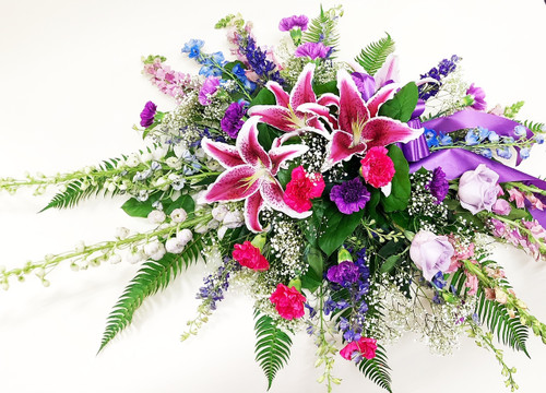 Gorgeous pink and purple mixed flowers styled as a casket sympathy spray. With locally grown lilies, premium purple roses, hot pink and purple carnations and other accent flowers, this is a perfect tribute to someone special.