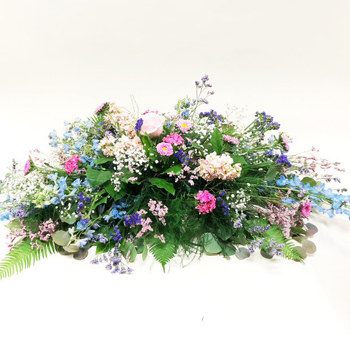 Bright summer wildflowers in pastel colors make up this beautiful fresh flower casket spray