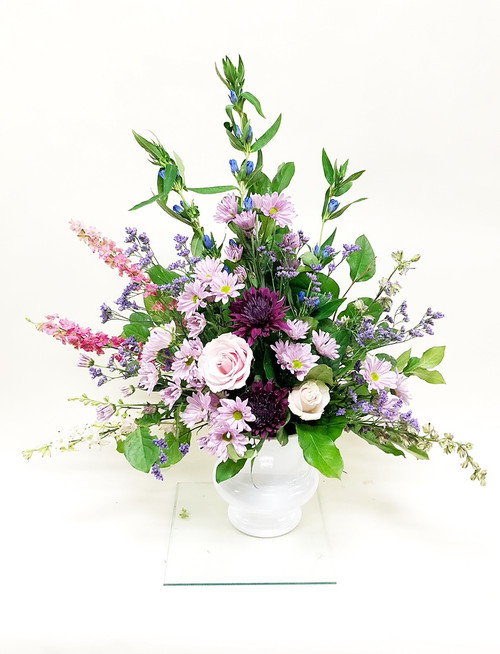 A service spray of mixed purples, pink and white flowers in a one-sided fan styled arrangement.