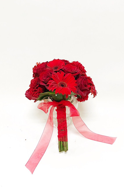 Bold all red bridal bouquet of gerbera and roses tied with coordinating ribbon.