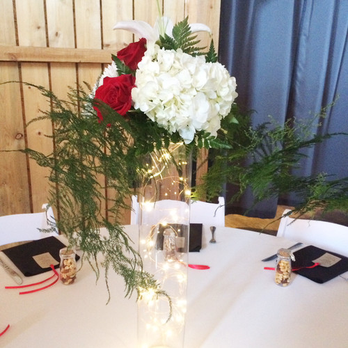 Need a stunner for your tables? Here is one with lights in the large glass cylinder with white hydrangea, red roses and cascading greens, will be the showstopper you're looking for!