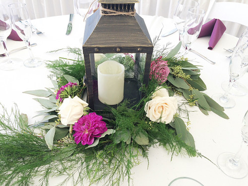 Flowers and greens add the perfect touch to your lantern centerpieces!