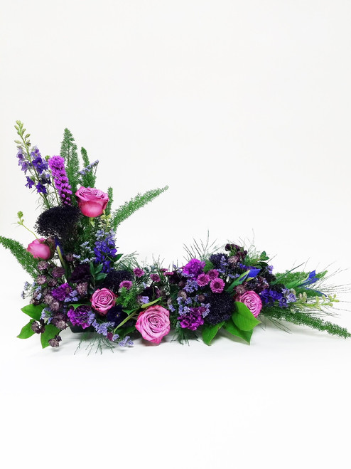 A mixture of purple flowers such as roses, mums, dianthus, and other purple accent flowers to tribute to frame your loved ones in memory.