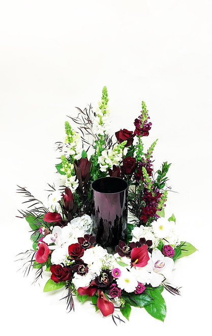 A sitting wreath to showcase the urn at the service. Designed with a variety of fresh flowers in red and white, including white hydrangea, red roses, red calla lilies.