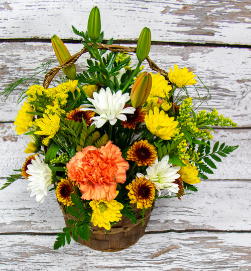 A mixture of fall colored flowers designed in a wicker basket.