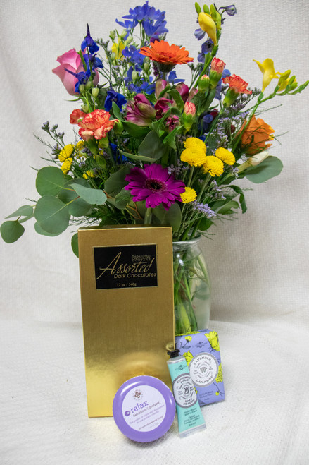 Send a bundle full of festive flowers and gifts for any occasion! This bundle features an upgraded Designer's choice flower arrangement, balloon (not pictured) moisturizing french floral soap and lotion, a scented candle and chocolates.