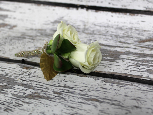 A uniquely designed boutonniere with a succulent, white roses and some bling! Wrapped in gold sparkle ribbon this design is soft but beautiful!