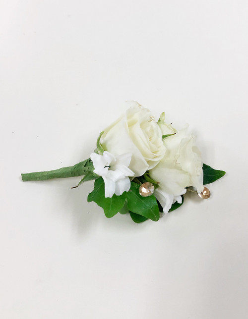 A white rose and hyacinth boutonniere designed with traditional ivy and added sparkle!