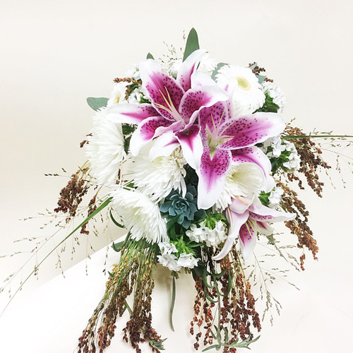 Beautiful and incredibly unique this lily bouquet features stargazers, spider mums and mixed grasses!  Perfect for your interesting fall wedding!