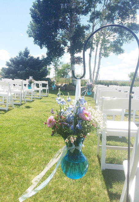 Fun aisle arrangement on a shepards hooks beside chairs, made up of wildflowers in a colorful vase.  Best part, can be used for reception decorations!!