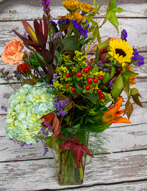 All of the fall colors in this beautiful mix! These Fresh flowers are seasonal and may include: Leucadendron, antique hydrangea, fall berries, and other mixed fresh flowers. A variety of flower types and a mix of fall colors!