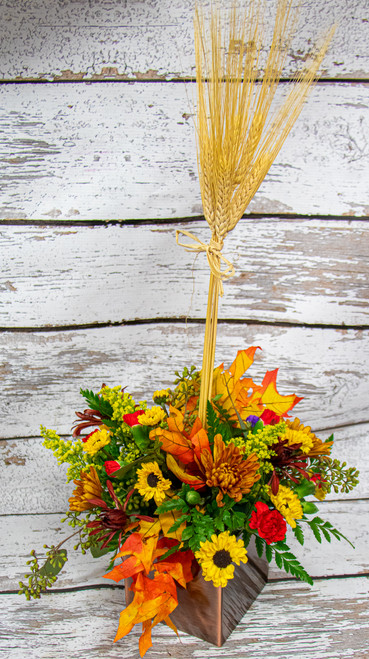 All of the fall colors in this festive mix! A fun wooden box container arranged with fall wheat, hypericum berries, and daisies in a topiary design! A variety of flower types and a mix of fall colors!