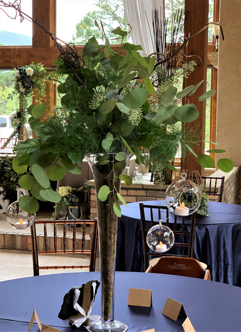 A gorgeous and simple wedding centerpiece designed with mixed greens, eucalyptus and a tall polish glass vase. A touch of light with tea light candles in hanging glass orbs.