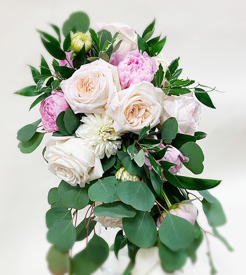 This gorgeous bouquet is designed with pastel pink peonies, white roses, spider mums and eucalyptus. A simple and soft mix of colors for a beautiful bouquet.