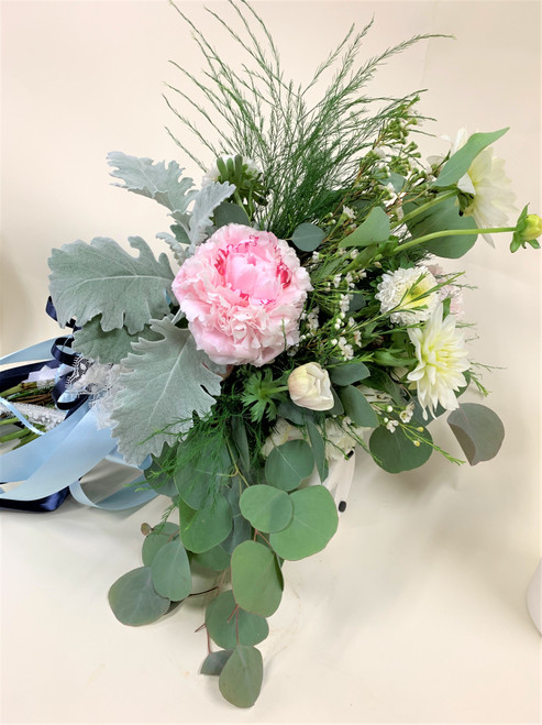 Pink peony, eucalyptus, and mixed greens in a free flowing hand-tied bridal bouquet.