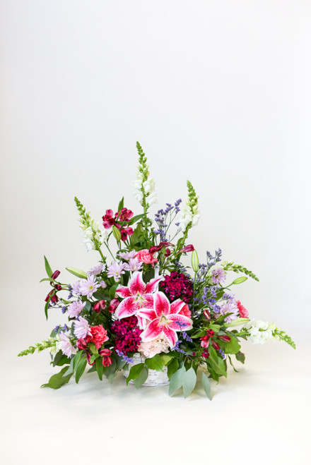 The Graceful Lady Sympathy Tribute is a one-sided arrangement with locally grown stargazer lilies. This basket arrangement is a classic pink display with other pink and purple accent colors.