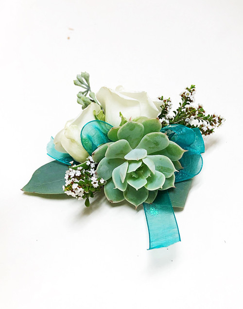 Succulent corsage with white filler and teal ribbon.