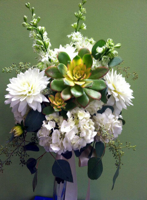 Succulents and the focus with complementing white flowers of  hydrangea, dahlias and larkspur.